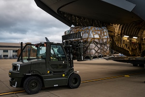 An Airman assigned to the 911th Logistics Readiness Squadron uses a forklift to load humanitarian aid for the Denton Program onto a C-17 Globemaster III at the Pittsburgh International Airport Air Reserve Station, Pennsylvania, March 11, 2021.