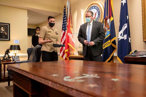 Builder 1st Class Hilary Lemelin, assigned to USS Constituition, speaks with Acting Secretary of the Navy Thomas W. Harker during a heritage desk presentation at the Pentagon in Washington D.C.