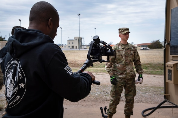 Lorenzo Burleson, A4C Strategic Communications, films Senior Airman Austin Davenport, 316th Civil Engineering Squadron electrical power production specialist, at Sheppard Air Force Base, Texas, March 24, 2021. The electrical power production career field is modernizing their career development courses, moving from paper study guides to interactive photos, videos and reviews online. (U.S. Air Force photo by Senior Airman Pedro Tenorio)