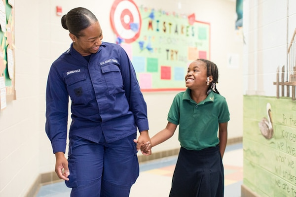 Lt. Tia Grandville walks down the hall of Gilliard Elementary School with a student. Grandville also acts a Partnership in Education Coordinator in Sector Mobile, Mobile, Alabama.