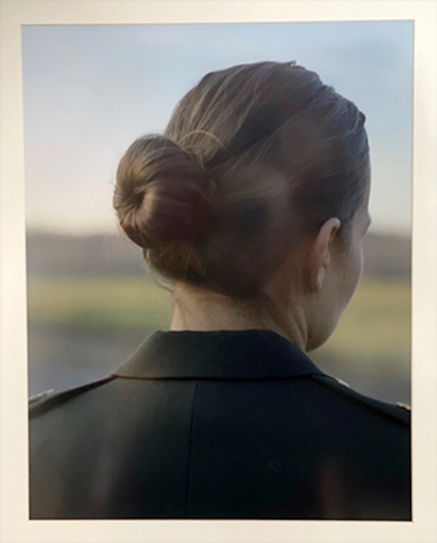 A photo of a woman from behind. Her hair is in a bun.