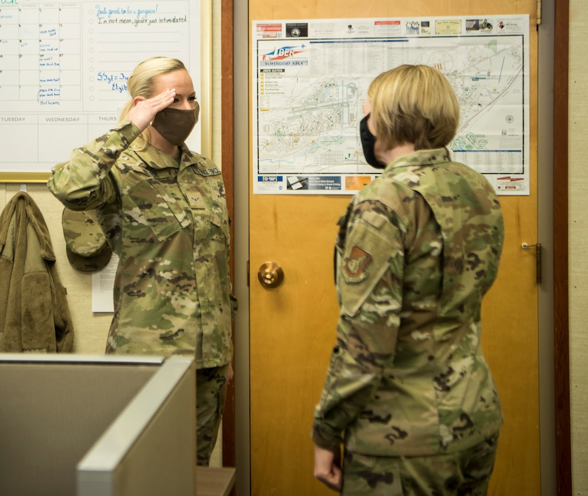 U.S. Space Force Specialist 3 Chanda Holter, a 673d Communications Squadron knowledge manager, salutes U.S. Air Force Col. Kirsten Aguilar, Joint Base Elmendorf-Richardson and 673d Air Base Wing commander, after receiving a coin during an immersion tour at JBER, Alaska, March 19, 2021. The focus of Aguilar's tour was to get to know the 673d CS Airmen and familiarize herself with the squadron's different sections and each one's role in supporting the base.