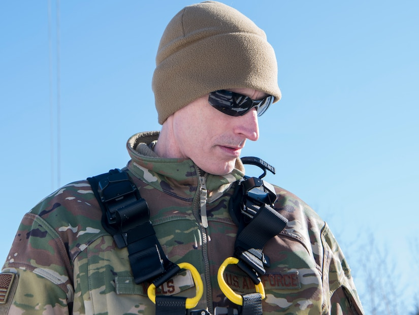 U.S. Air Force Chief Master Sgt. Lee Mills, 673d Air Base Wing command chief, puts on a harness during a 673d Communications Squadron immersion tour at Joint Base Elmendorf-Richardson, Alaska, March 19, 2021. The tour focused on the 673d CS Airmen and their role supporting JBER's mission.