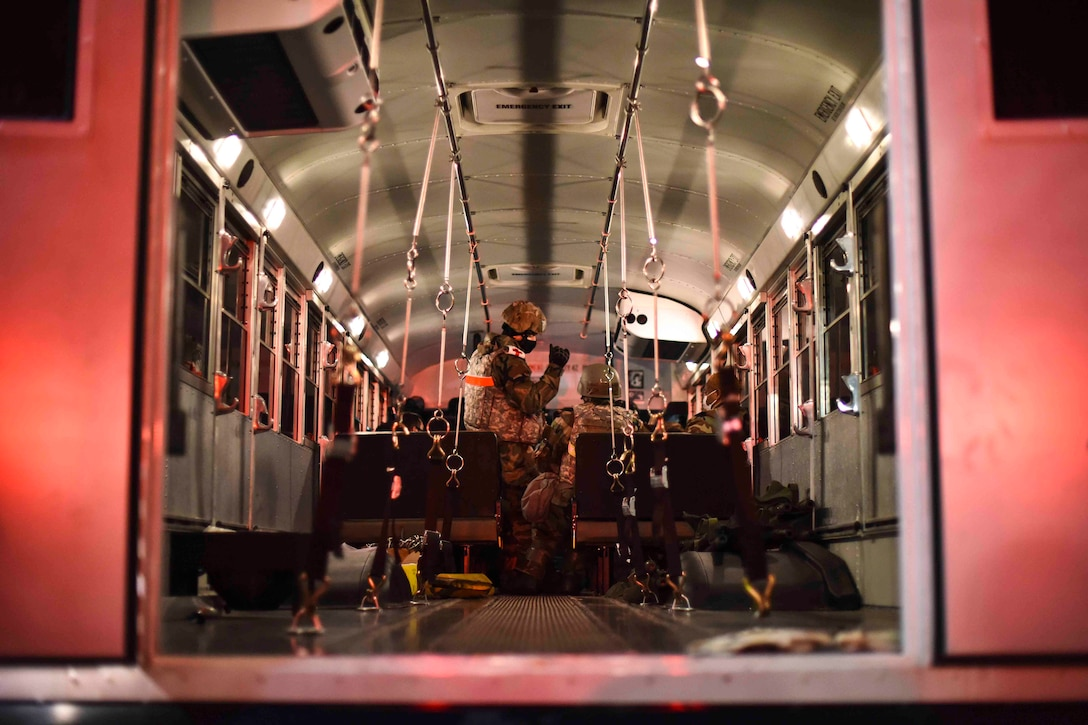 An airman stands inside a bus as others sit around.