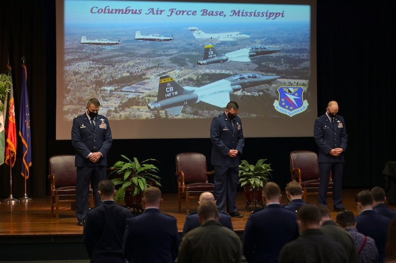 Col. Seth Graham (left), 14th Flying Training Wing commander, Col. Jeffrey Welborn (middle), 14th Mission Support Group commander, and Lt. Col. Joseph McCane (right), 14th Student Squadron commander, lower their head in prayer at the beginning of the graduation ceremony, March 26, 2021, on Columbus Air Force Base, Miss. The 14th FTW conducts Specialized Undergraduate Pilot Training for U.S. Air Force and allied officers, as well as tactical training for Afghan and Lebanese pilots and aircraft maintainers in the A-29 Super Tucano at Moody AFB, Georgia. (U.S. Air Force photo by Senior Airman Jake Jacobsen)