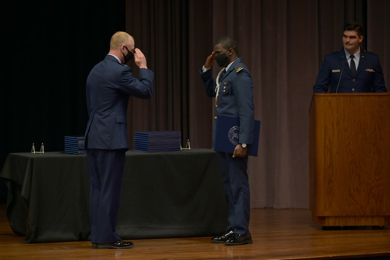 Col. Seth Graham (right), 14th Flying Training Wing commander, returns a salute from 1st Lt. Abubakar Alkali, international student pilot graduate, March 26, 2021, on Columbus Air Force Base, Miss. In the primary phase of training, students learn basic aircraft control, including takeoff and landing techniques and aerobatics in all types of weather to several different locations. (U.S. Air Force photo by Senior Airman Jake Jacobsen)