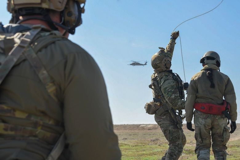A man and woman prepare to be hoisted up into a helicopter