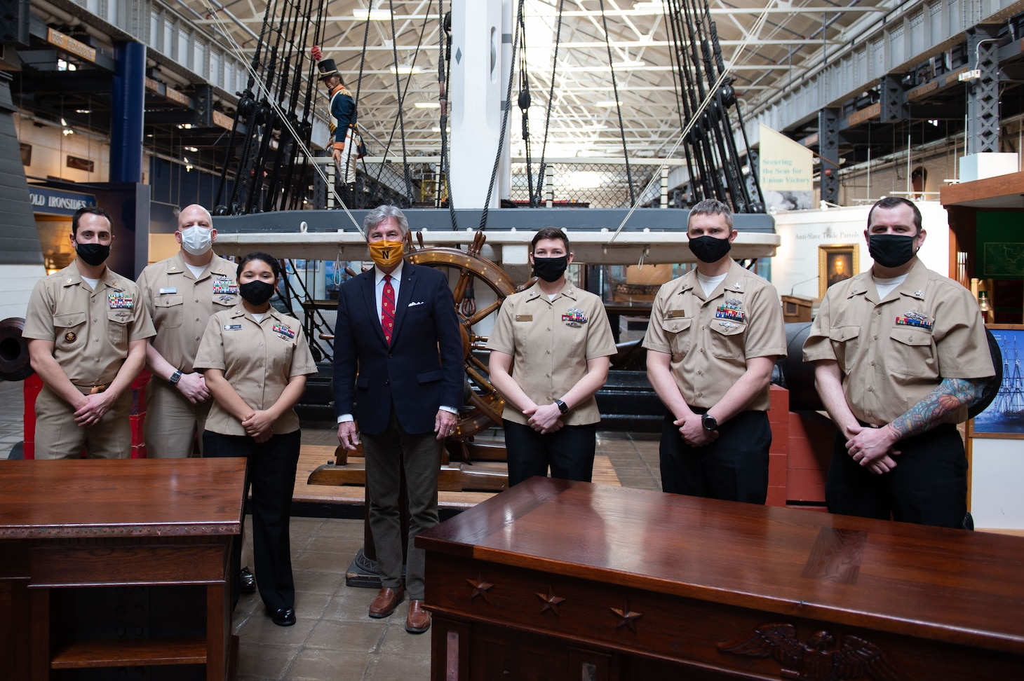 Former Secretary of the Navy, Kenneth J. Braithwaite, poses with Seabees during an executive desk presentation event at the National Museum of the U.S. Navy.