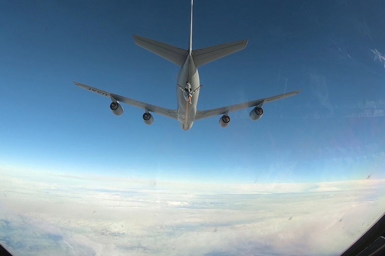 Photo of a KC-135 Stratofortress flying with its fuel boom extended.