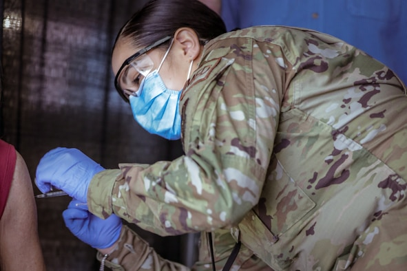 Airman 1st class Elizabeth Chavez, 66th Medical Squadron technician, administers a COVID-19 vaccination at the state-run, federally-supported Ford Field Community Vaccination Center in Detroit, March 24. . Members of the 66 MDS at Hanscom Air Force Base, Mass., deployed to Detroit as part of the federal effort to support the COVID-19 vaccination response to vaccinate up to 6,000 people a day. (U.S. Army photo by Spc. Laurie Ellen Schubert)