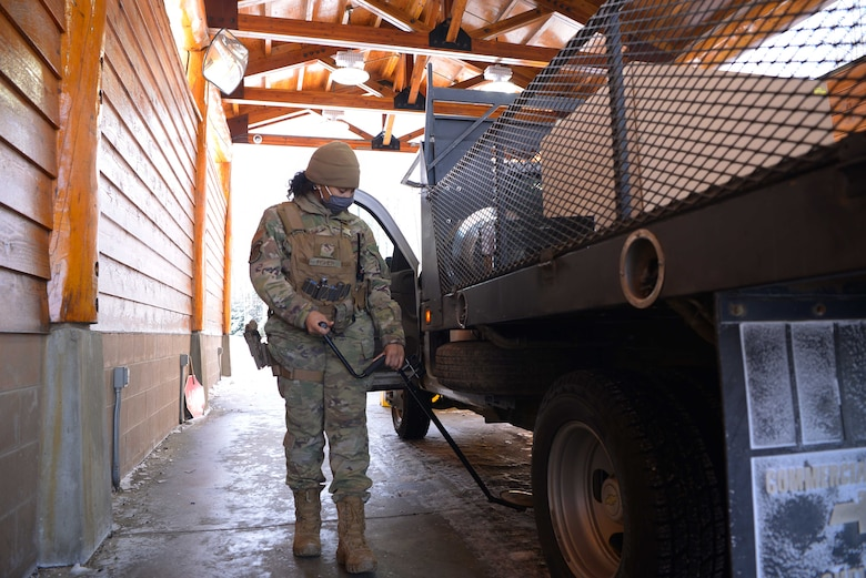 U.S. Air Force Senior Airman Heaven Fisher, a 354th Security Forces Squadron response force leader, searches a vehicle for explosives and contraband March 16, 2021, on Eielson Air Force Base Alaska. Security Forces defenders are responsible for protecting Air Force families and property 24/7 by providing law enforcement and security services. (U.S. Air Force photo by Senior Airman Beaux Hebert)