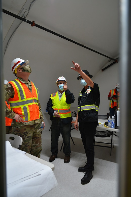 Ola Ostlund with HALLSTA Inc., right, points out a feature inside an alternate care facility built by the Corps and its contractors, to Brig. Gen. Paul Owen, commander of the U.S. Army Corps of Engineers South Pacific Division, left, while Jamil Abuniaj, civil engineer with the Corps' LA District, looks on during a March 19 tour of the project site at Adventist Health White Memorial Medical Center in the Boyle Heights neighborhood of Los Angeles.