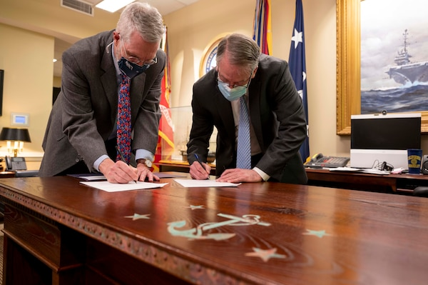 Acting Secretary of the Navy Thomas W. Harker, right, signs a letter of authenticity for the newly designed heritage desk for the office of the Secretary of the Navy at the Pentagon in Washington D.C.