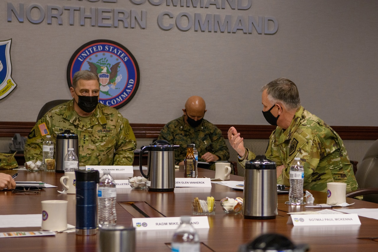 Military personnel hold a discussion with a general.
