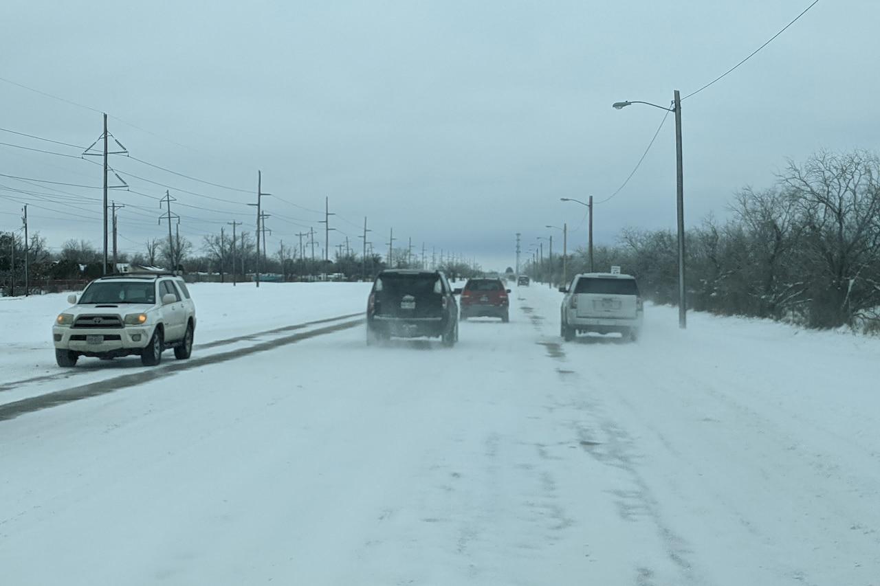 Cars drive on a snowy street.