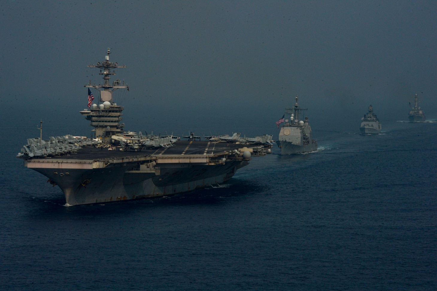 INDIAN OCEAN (March 28, 2021) – The aircraft carrier USS Theodore Roosevelt (CVN 71), front, the Ticonderoga-class guided-missile cruiser USS Bunker Hill (CG 52), center right, the Indian Navy Shivalik-class guided-missile frigate INS Shivalik (F47), right, and the Arleigh Burke-class guided-missile destroyer USS Russell (DDG 59), sail in formation March 28, 2021. The Theodore Roosevelt Carrier Strike Group is on a scheduled deployment to the U.S. 7th Fleet area of operations. As the U.S. Navy's largest forward-deployed fleet, 7th Fleet routinely operates and interacts with 35 maritime nations while conducting missions to preserve and protect a free and open Indo-Pacific Region. (U.S. Navy photo by Mass Communication Specialist Seaman Eduardo A. Torres)