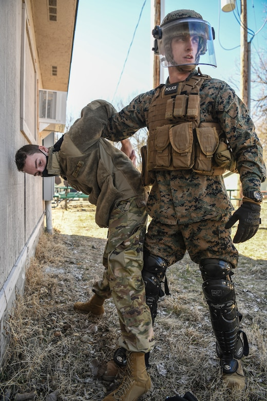 Lance Corporal Colton Sabrowski, Charlie Company, 4th Law Enforcement Battalion Wright-Patterson Air Force Base, Ohio, searches Senior Airman Scott Araujo, 445th Security Forces Squadron, WPAFB, for any dangerous or unlawful items during a training exercise at the Warfighter Training Center here March 6th, 2021. Both Marines and Airmen participated in the detainee operations training adding elements of experience from each branch of service providing total force integration. This experience provides an opportunity for each branch involved to learn and benefit from each other's techniques. (U.S. Air Force photo by Master Sgt. Patrick OReilly)