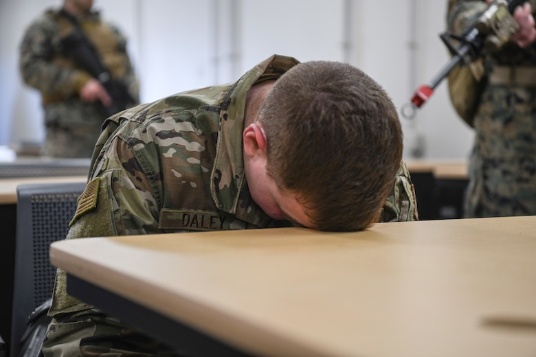 Staff Sgt. Justin Daley, 445th Security Forces Squadron, holds his head against a desk as an acting 'detainee' during a training exercise at the Warfighter Training Center here March 6th, 2021, Wright-Patterson Air Force Base, Ohio. Marines from Charlie Company, 4th Law Enforcement Battalion and Airmen from the 445th Security Forces Squadron participated in the detainee operations training adding elements of experience from each branch of service providing total force integration.