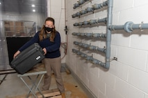 Photo of A woman stands in an industrial work area. The area appears to be a concrete chamber, with metal racks on the wall with spigots attached. The woman, wearing a mask and goggles for safety, is loading a black square case onto a base apparatus.
