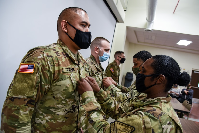 First Sgt. Ebony Bridges promotes one of her Soldiers during ceremony held March 24, 2021, in Richmond, Virginia. Bridges is assigned to Bravo Company of the Virginia National Guard's Recruiting and Retention Battalion. (U.S. Army National Guard photo by Sgt. 1st Class Terra C. Gatti)