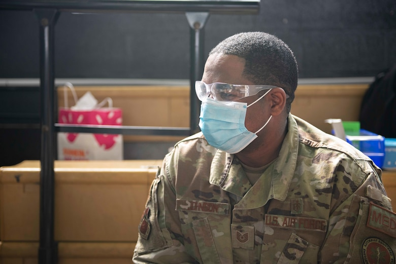 Tech. Sgt. Edric Johnson, an El Paso, Texas, native and 335th Expeditionary Medical Operations Squadron vaccinator, prepares to vaccinate a community member at a Community Vaccination Center in Brooklyn, N.Y., March 22, 2021. Johnson is deployed from the 56th Medical Group out of Luke Air Force Base, Ariz., and is one of approximately 140 Airmen across 28 installations deployed to the Brooklyn CVC in support of U.S. Army North's COVID-19 response efforts. (U.S. Air Force photo by Tech. Sgt. Ashley Nicole Taylor)
