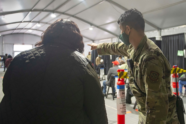 Senior Airman Joshua Acosta, a Roswell, N.M., native and 335th Expeditionary Medical Operations Squadron general purpose Airman, ushers a community member at a Community Vaccination Center in Brooklyn, N.Y., March 22, 2021. Acosta is deployed from the 6th Force Support Squadron out of MacDill Air Force Base, Fla., and is one of approximately 140 Airmen across 28 installations deployed to the Brooklyn CVC in support of U.S. Army North's COVID-19 response efforts. (U.S. Air Force photo by Tech. Sgt. Ashley Nicole Taylor)