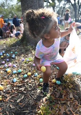 Zaniyah Mason, daughter of U.S. Air Force Tech. Sgt. Meagan Mason, 403rd Maintenance Group unit training manager, picks up an Easter Egg during Keesler's Eggstravaganza at the marina park at Keesler Air Force Base, Mississippi, March 27, 2021. The 81st Force Support Squadron hosted the event for military children. (U.S. Air Force photo by Kemberly Groue)