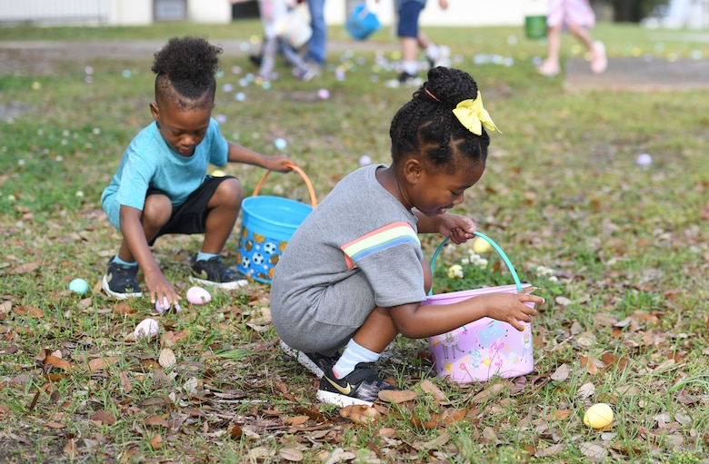 Kylan and Caris Campbell, children of U.S. Air Force Maj. Alecia Campbell, 81st Contracting Squadron commander, pick up Easter eggs during Keesler's Eggstravaganza at the marina park at Keesler Air Force Base, Mississippi, March 27, 2021. The 81st Force Support Squadron hosted the event for military children. (U.S. Air Force photo by Kemberly Groue)