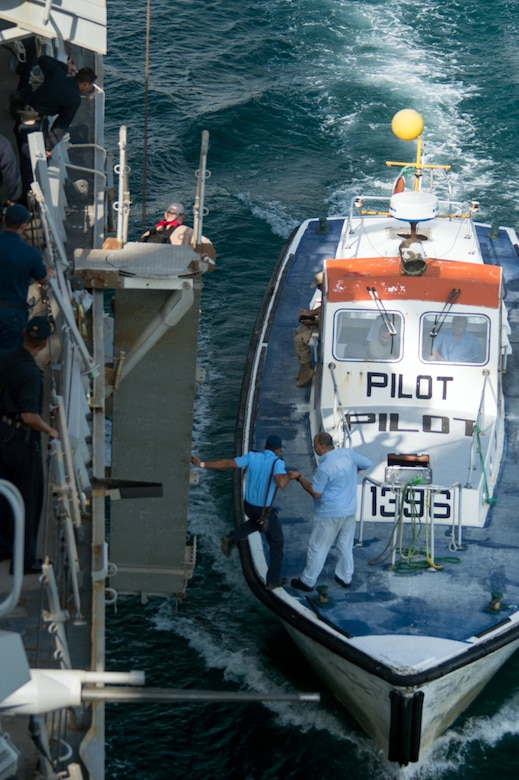 """A small boat, with the word """"pilot"""" written on the front, pulls alongside a larger vessel. Men move between the vessels."""