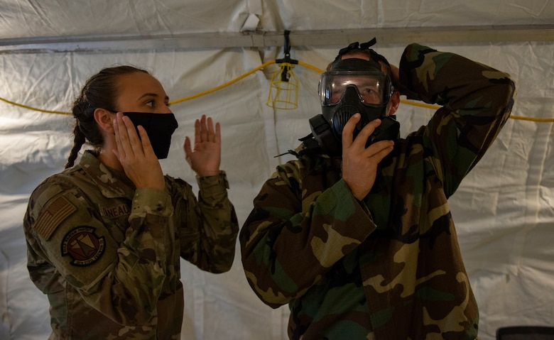 U.S. Air Force Airman 1st Class Maria Daneault, an emergency management apprentice assigned to the 36th Civil Engineer Squadron, instructs U.S. Air Force Senior Airman James Fink how to don his mask during Chemical, Biological, Radiological, Nuclear and Explosives defense training at Andersen Air Force Base, Guam, March 25, 2021.
