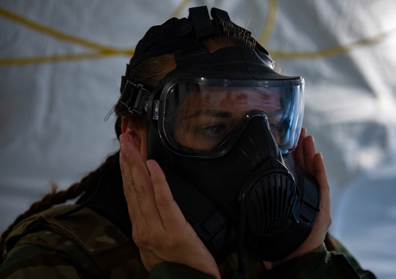 U.S. Air Force Airman 1st Class Maria Daneault, an emergency management apprentice assigned to the 36th Civil Engineer Squadron, performs a negative pressure test on her mask during Chemical, Biological, Radiological, Nuclear and Explosives defense training at Andersen Air Force Base, Guam, March 25, 2021.