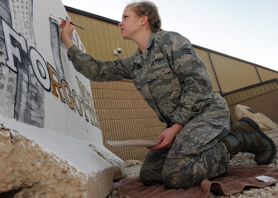 """Senior Airman Adrianna Recine, 379th Expeditionary Medical Group laboratory technician, volunteers her time to refurbish the 9/11 barrier memorial here, March 21. """"I volunteered to paint the 9/11 wall to show those who sacrificed their lives were not forgotten,"""" Recine said. Recine is deployed from the 633rd Medical Support Squadron at Joint Base Langley-Eustis, Va. (U.S. Air Force photo/Senior Airman Joel Mease)"""