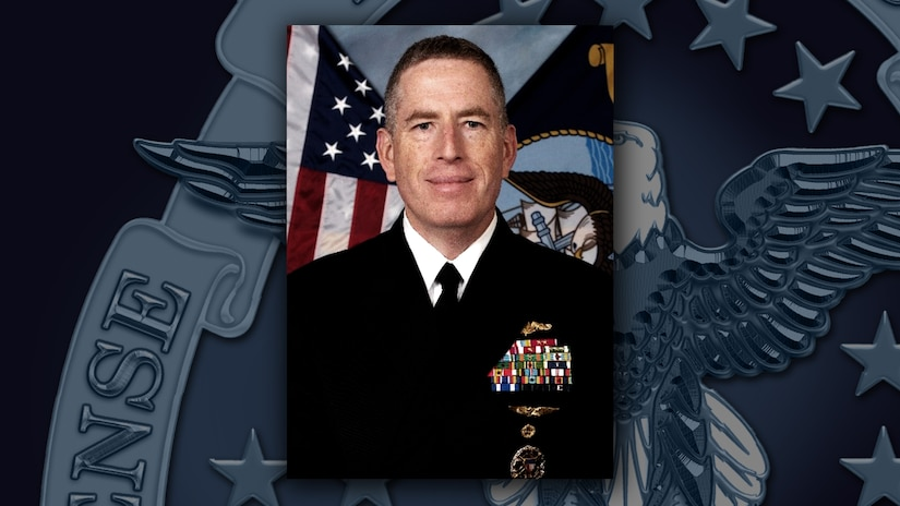 White man in dress uniform with medals and ribbons in front of the US flag.