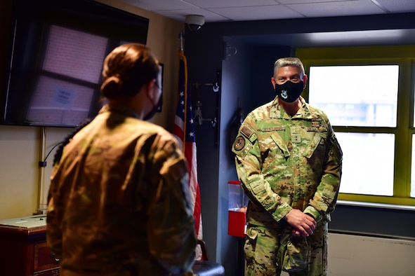 Military Training Leader provides dormitory overview to general.