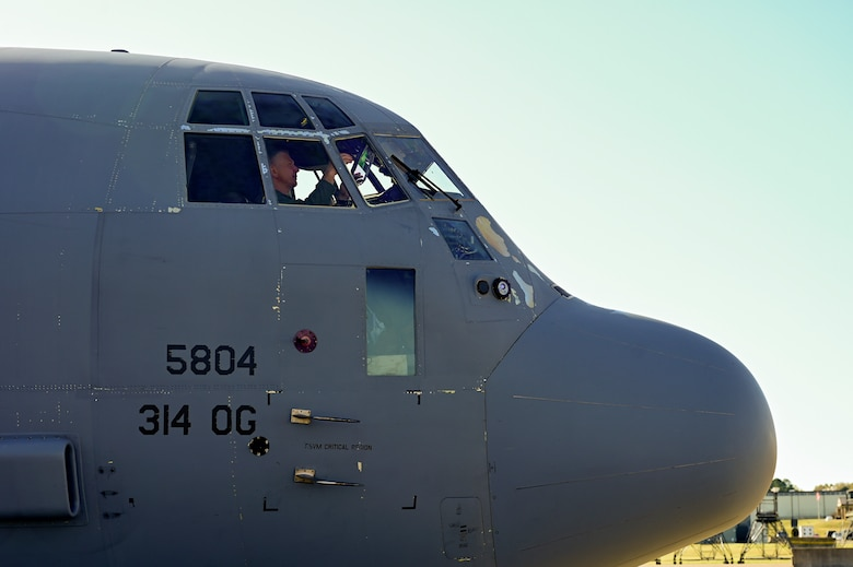 A pilot conducts pre-flight checks on a C-130J Super Hercules.