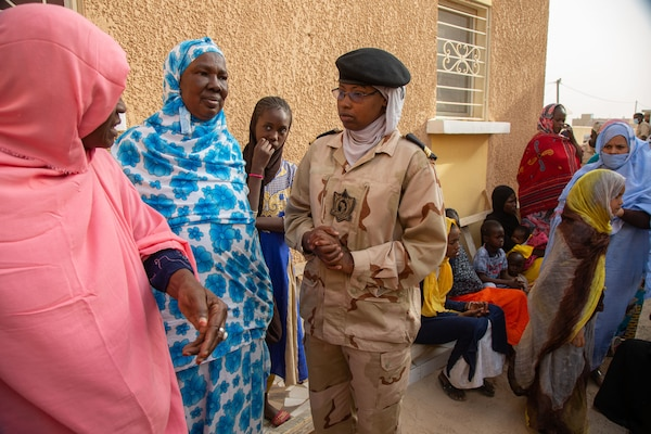 Mauritanian woman soldier speaks with women in colorful dresses outside a clinic.