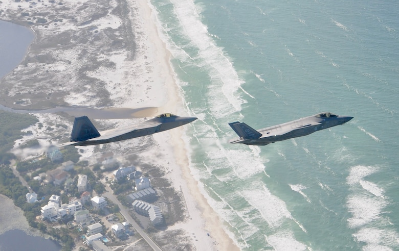 A F-22 Raptor and a F-35 Lightning II fly over the beach