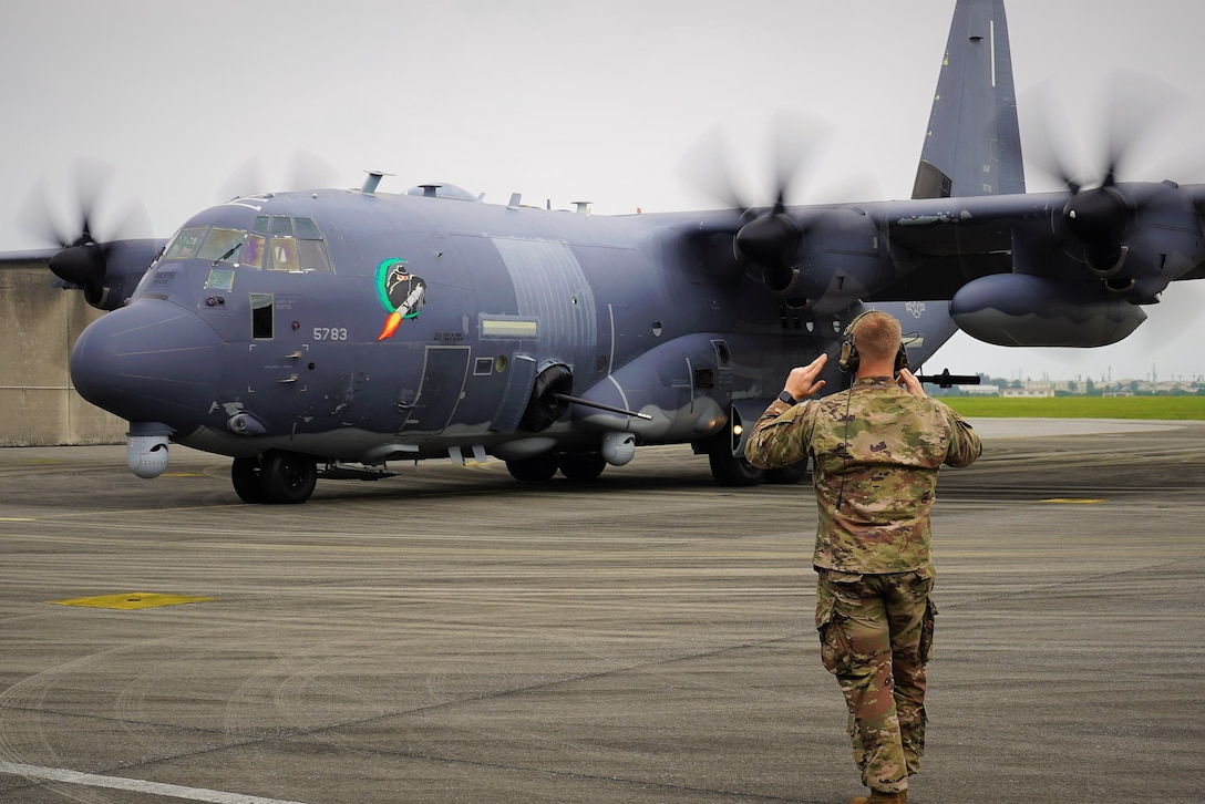 An Airman from the 73rd Special Operations Squadron marshals an AC-130J Ghostrider to its parking location after landing at Kadena Air Base.