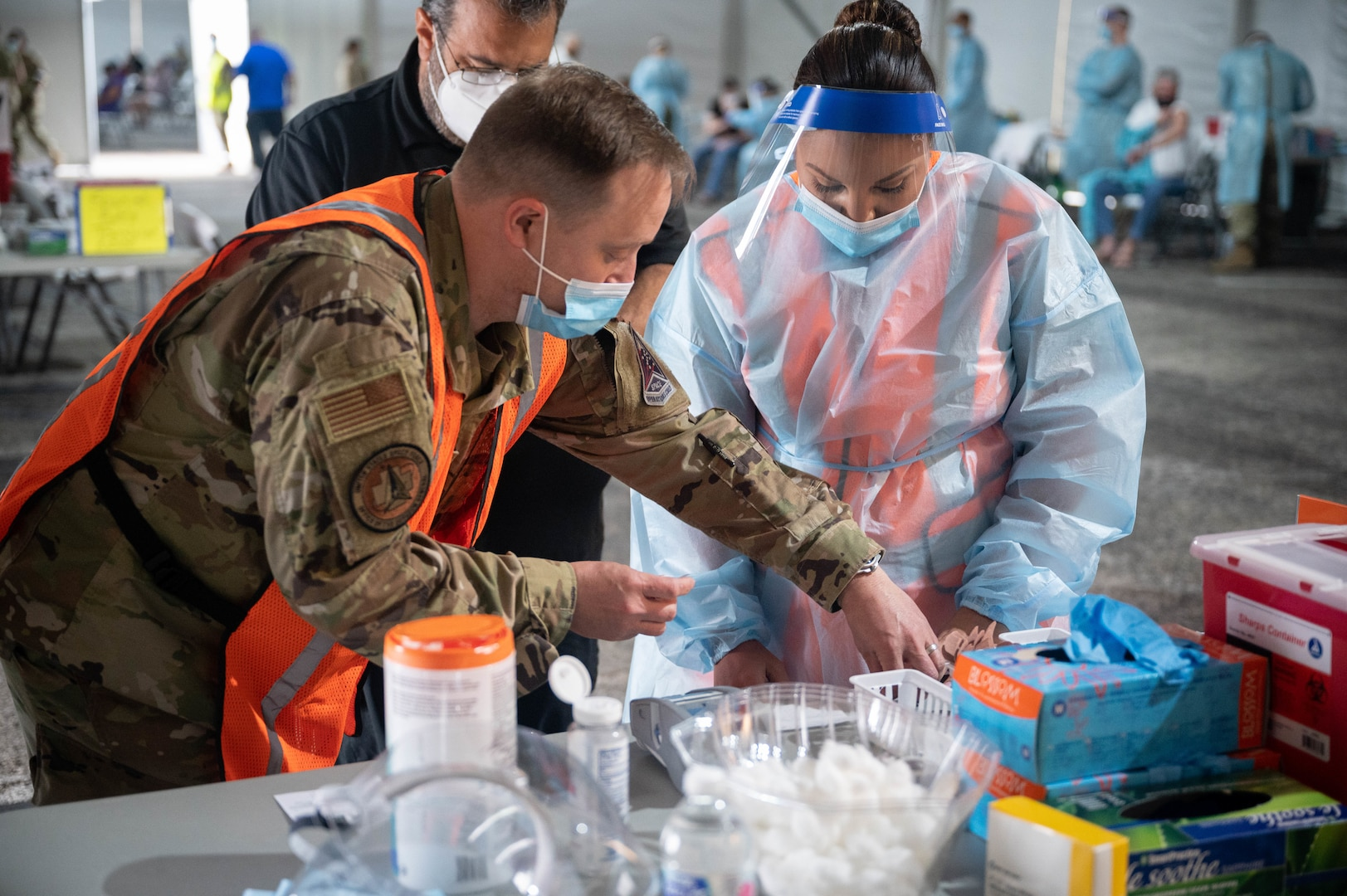 U.S. Air Force Maj. Michael Jessup (left) assists U.S. Air Force Tech. Sgt. Jerrica Wild (right), both deployed from Peterson Air Force Base, Colorado, with paper work in preparation for vaccine distribution at the Tampa Community Vaccination Center in Tampa, Florida, March 3, 2021. Jessup and Wild are two of nearly 140 Airmen on site at the state-led, federally-supported operation. U.S. Northern Command, through U.S. Army North, remains committed to providing continued, flexible Department of Defense support to the Federal Emergency Management Agency as part of the whole-of-government response to COVID-19. (U.S. Air Force photo by Master Sgt. Holly Roberts-Davis/Luke AFB Public Affairs)