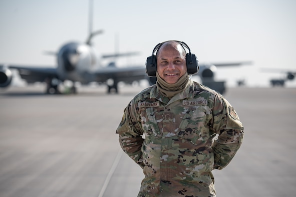 a man poses for a portrait in uniform on a flightline