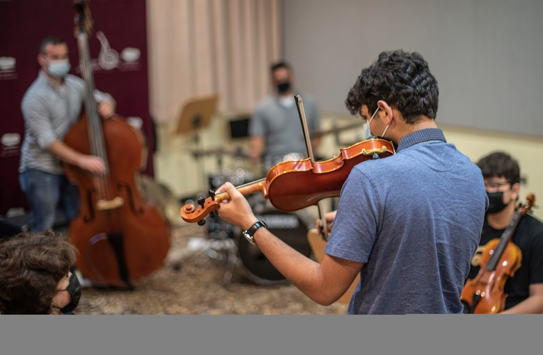 A Qatar Music Academy student improvises with the U.S. Air Forces Central Band with a specially tuned violin at the academy in Doha, Qatar, March 24, 2021. The AFCENT Band perform and tour in small ensembles throughout the region to promote positive troop morale, diplomacy and outreach to host-nation communities. (U.S. Air Force photo Tech. Sgt. Travis Edwards)