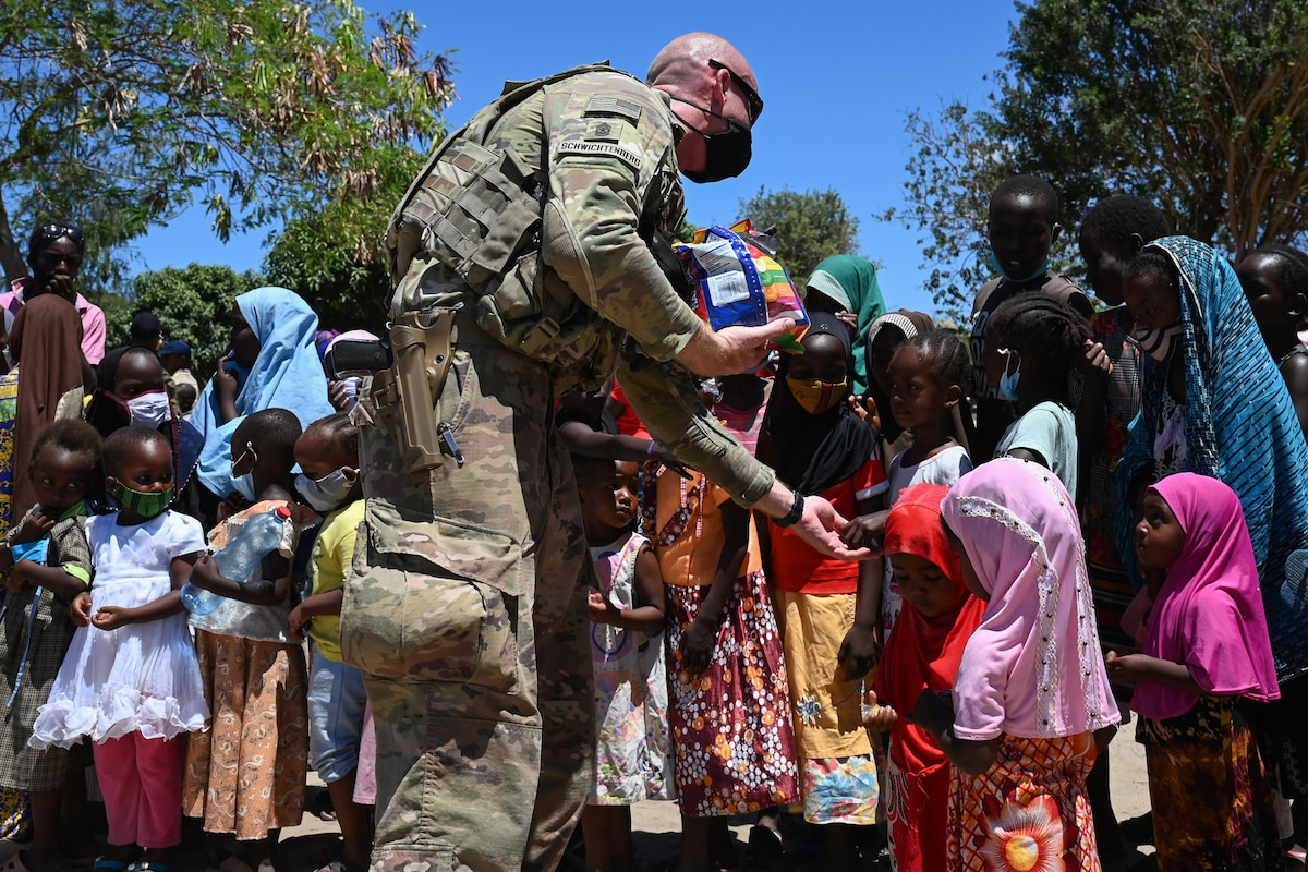 A soldier hands out candy to a group of children.