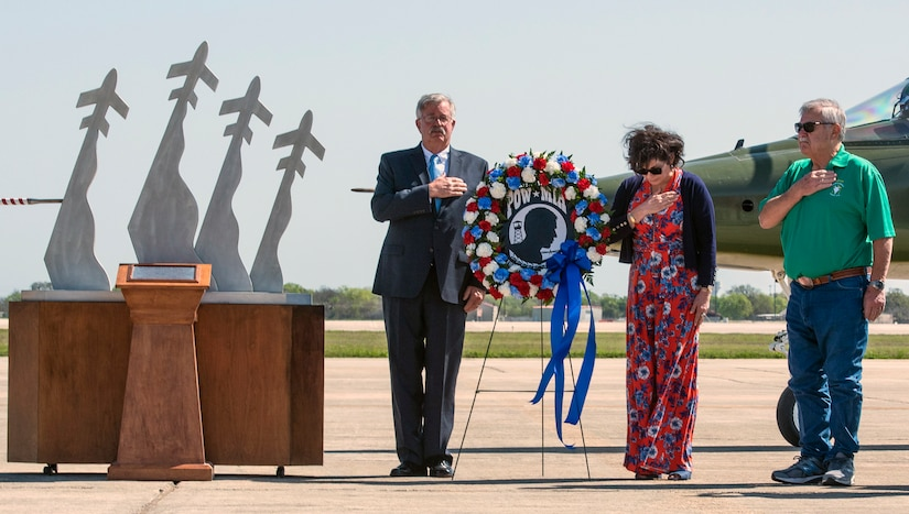 Former prisoners of war retired Capt. Gregg Hanson (left) and retired Maj. Richard Bates (right) are joined by Janine Sijan in a moment of silence to honor prisoners of war during the Freedom Flyers wreath-laying ceremony at Joint Base San Antonio-Randolph March 26. Janine is the sister of Capt. Lance P. Sijan, a Medal of Honor recipient who lost his life as a POW in Vietnam. The 560th Flying Training Squadron holds the annual Freedom Flyers Reunion, which gives prisoners of war a chance to take their final flights and honor those who are unable to. This year was the 47th Freedom Flyers Reunion.