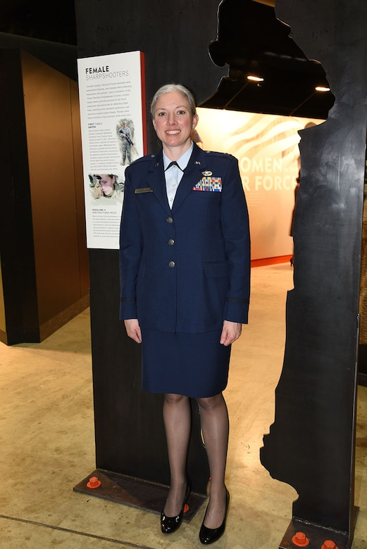 Illinois Air National Guard Capt. Jennifer Weitekamp poses next to the Women in the Air Force exhibit honoring her accomplishment at the National Museum of the U.S. Air Force March 5.