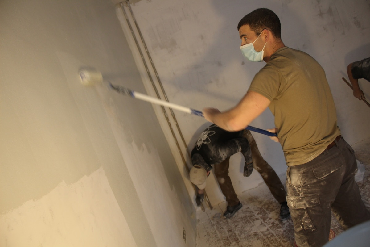 A soldier uses a roller to paint a wall.