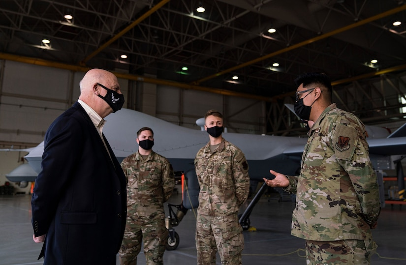 Acting Secretary of the Air Force John Roth interacts with Airmen by an MQ-9 Reaper.