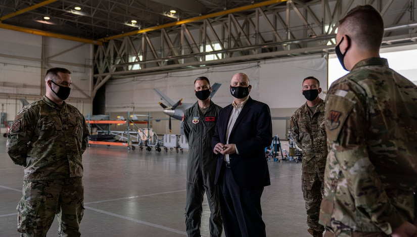 Acting Secretary of the Air Force John Roth interacts with Airmen in a hangar.