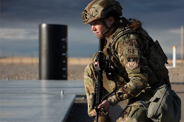 A female defender takes a knee while on duty while holding a rifle at a launch facility.