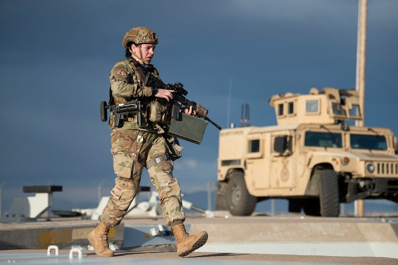 A female defender moves across the launch facility carrying a rifle and an ammo container, with a Humvee in the background.