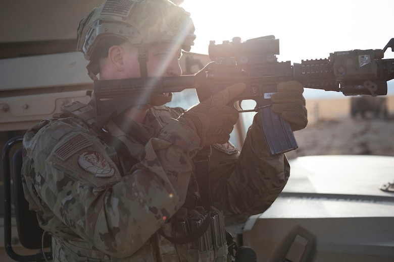 A defender stands with his rifle raised looking towards the right side of the fame. He is pointing down range, sun is shining brightly in the background of the image.